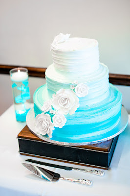 turquoise and white wedding cake on wooden stand