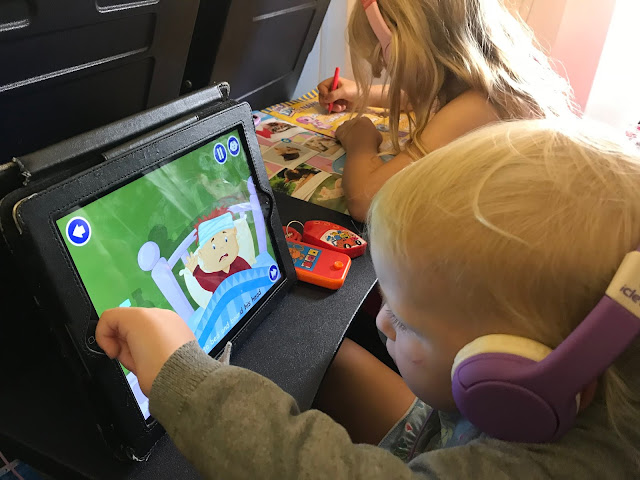 two children on an aeroplane, one is playing on the iPad, the other is writing in a magazine and listening to her ipod