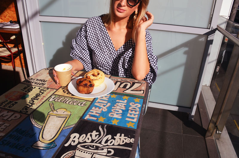 girl wearing gingham wrap blouse with breakfast pastries on balcony