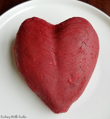 red velvet cheese ball hand shaped into a heart shape, ready to be coated in white chocolate