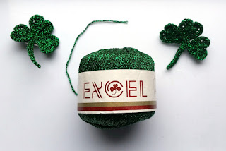 "Front-view of skein of metallic yarn. The white label has red lettering ""EXCEL"" and a gold and red horizontal stripe underneath the brand name.  There is a silhouette of a shamrock printed in the 'bowl' or inside space of the letter ""c"". The skein is flanked by two completed crocheted shamrocks, one in each top corner of the photograph."