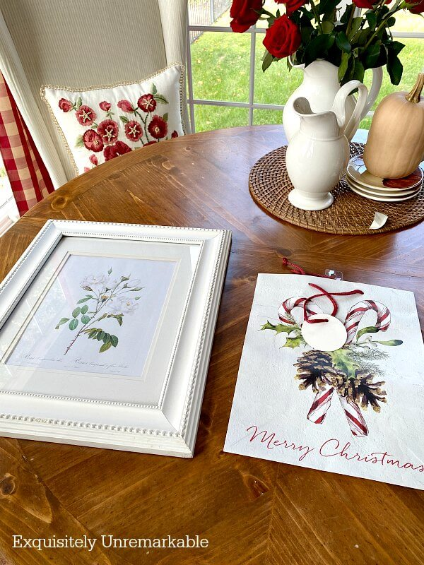 White picture frame and Christmas gift bag on table
