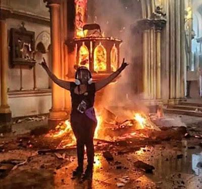 Moça comemora incêndio numa igreja histórica de Santiago de Chile
