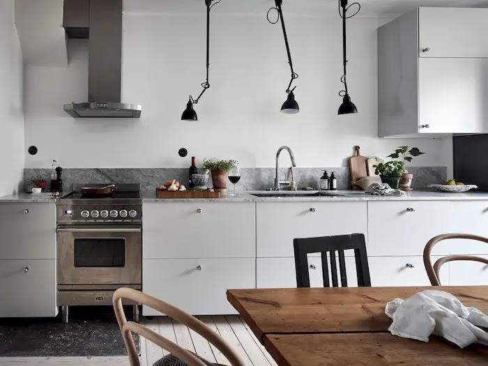 cocina nórdica con encimera de mármol gris y lámparas colgantes negras