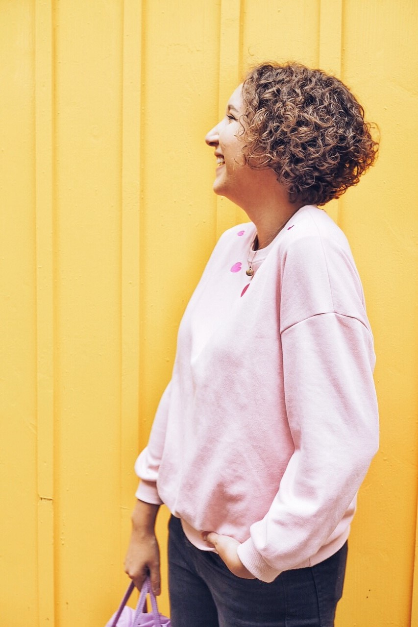 Pink jumper on yellow background