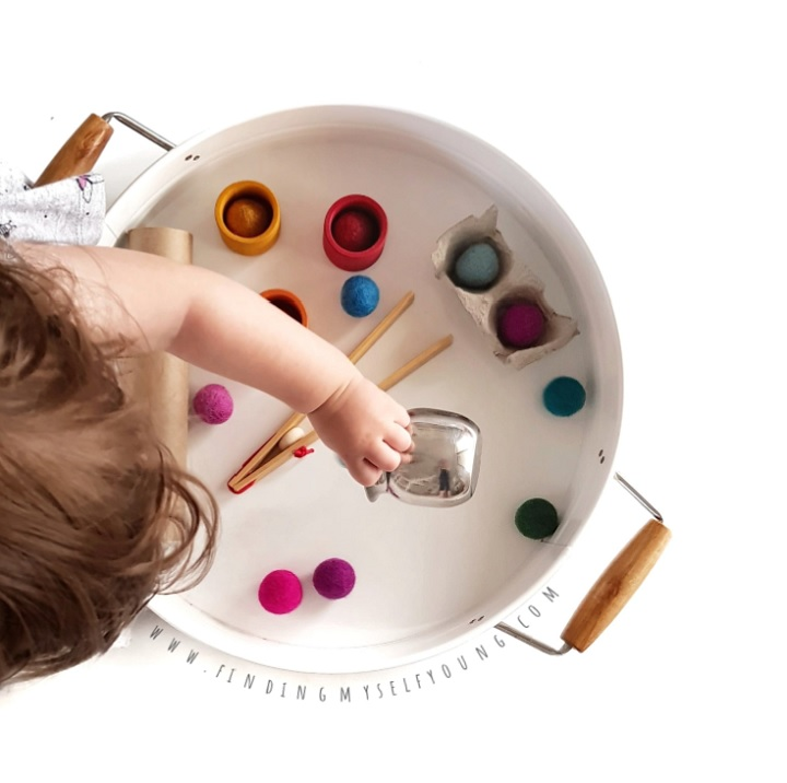 toddler playing with pom poms and cups in a tray