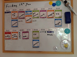 Photograph of a magnetic board with a time table with magnets with times on and colourful magnets that make up the time table. There are also written notes on the time table. Also on the magnetic board is a pen and some magnets.