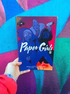 Paper Girls Vol.5 by Brian K. Vaughan being held in front of street art