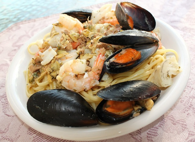 this is a plate of linguine pasta with a white clam sauce topped with a medley of seafood. There are mussels, clams and crab in this pasta dish