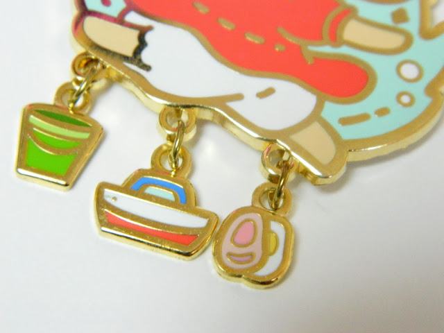 A photo of three charms on an enamel pin of Studio Ghibli character Ponyo, a green bucket, a toy boat and a egg and pork piece from the japanese dish ramen
