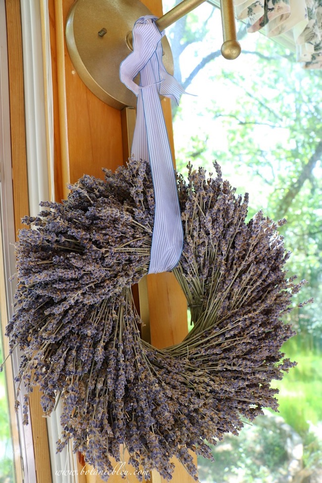 French Country Sunspace Update includes a dried lavender wreath hanging from a blue and white striped ribbon between windows