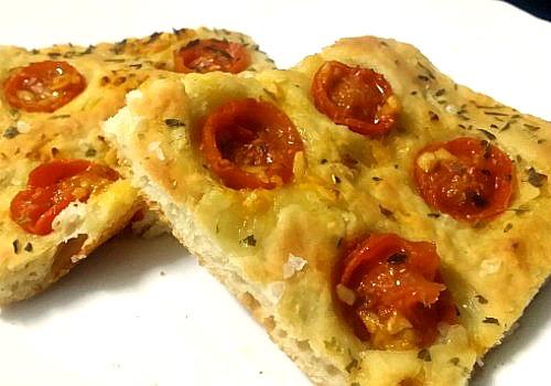 Una especie de pizza con tomates cherry y hierbas aromáticas