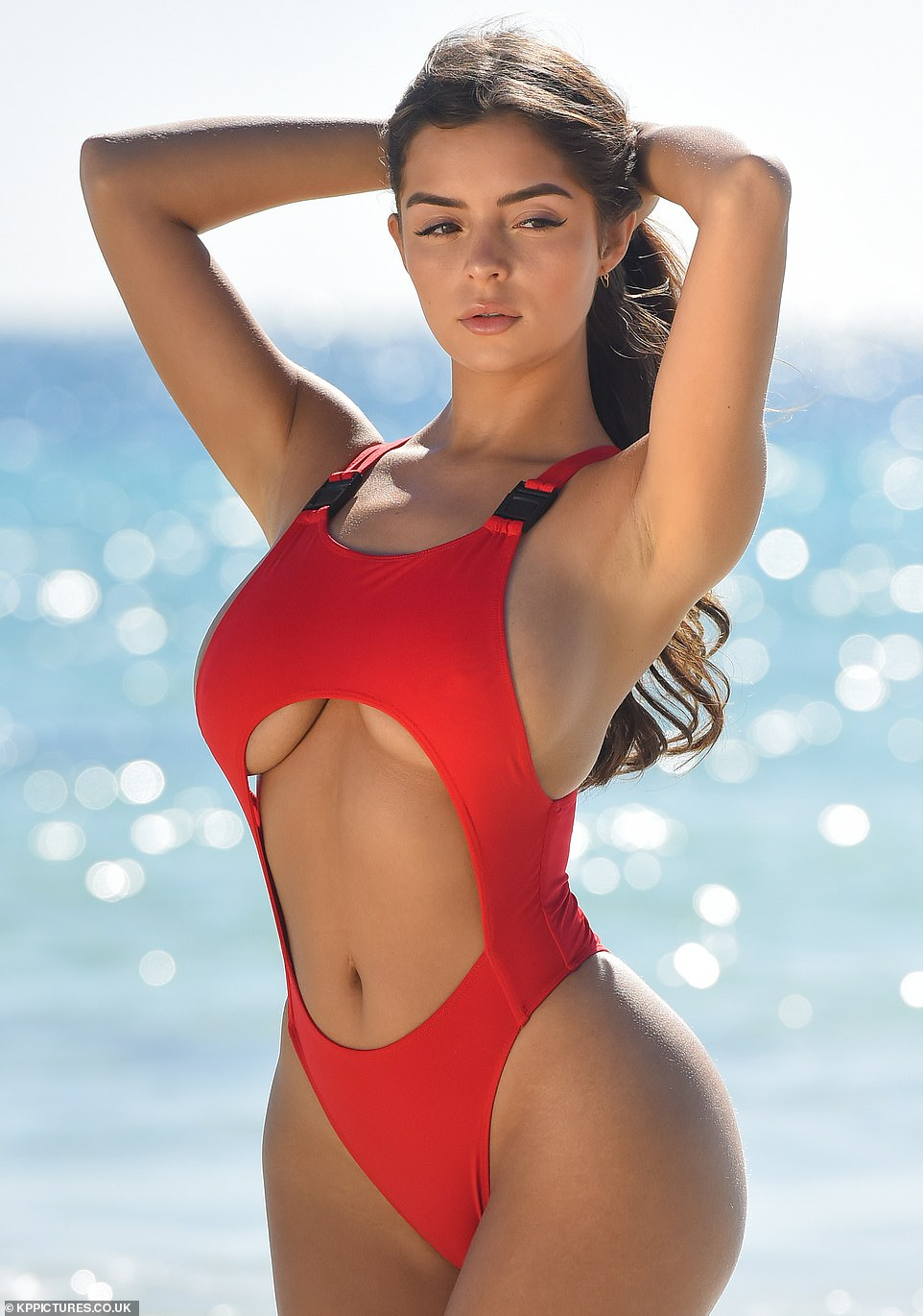Voluptuous model displays her underboob in a very revealing red swimsuit