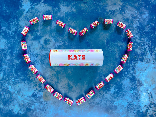 "A white tube with pictures of love hearts on and the name ""KATE"" personalised on it in side a heart shape made from mini packets of Love Hearts"