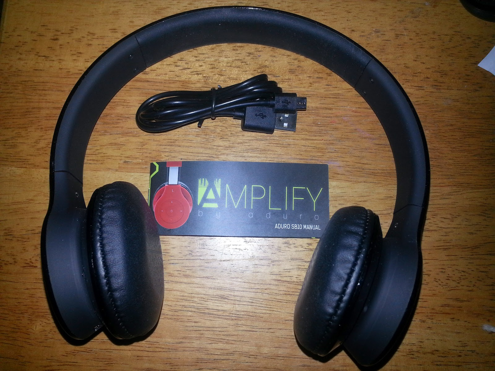 5653d48f62a The AMPLIFY SB10 with everything that comes in the package (a charger cord  and an easy-to-read