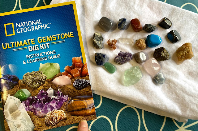 The Ultimate Gemstone Dig Kit Instructions and Learning guide next to the 20 gemstones found in our set including: agate, quartz, tiger's eye, snowflake obsidian, amethyst, aragonite, aventurine, hematite, desert rose, a geode piece, green fluorite, pyrite, red jasper, sodalite, turquenite, blue calcite and labradorite