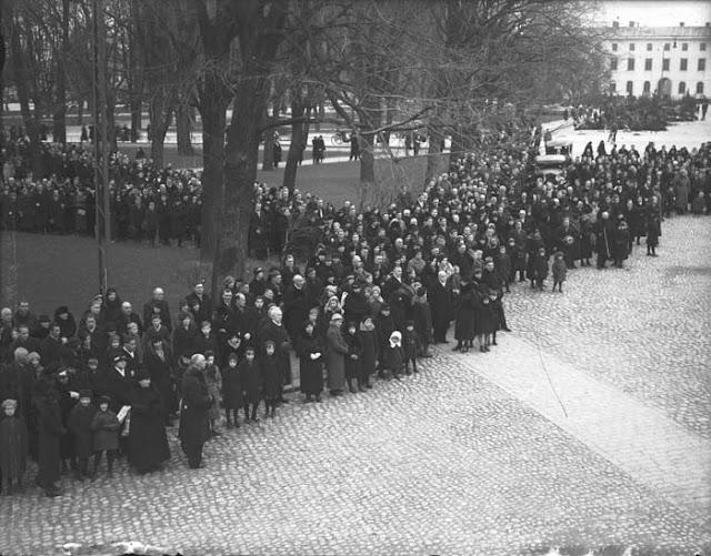 Ihmisjoukko seisoo aukiolla ja puiston reunalla.