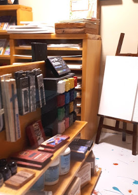 One-twelfth scale modern miniature art store displaying various paints, mark-making material and supports.