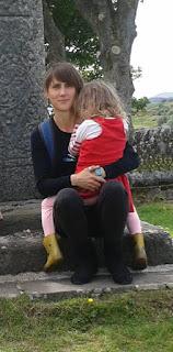 žena s dieťaťom na rukách, v pozadí keltský kríž