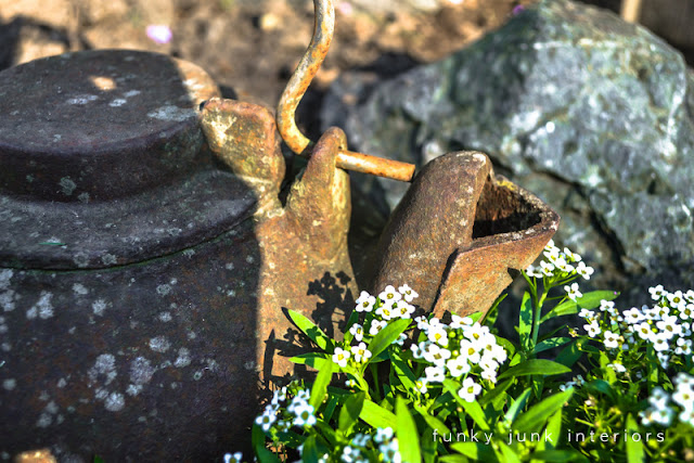 An old kettle as garden art sitting in a flower bed.