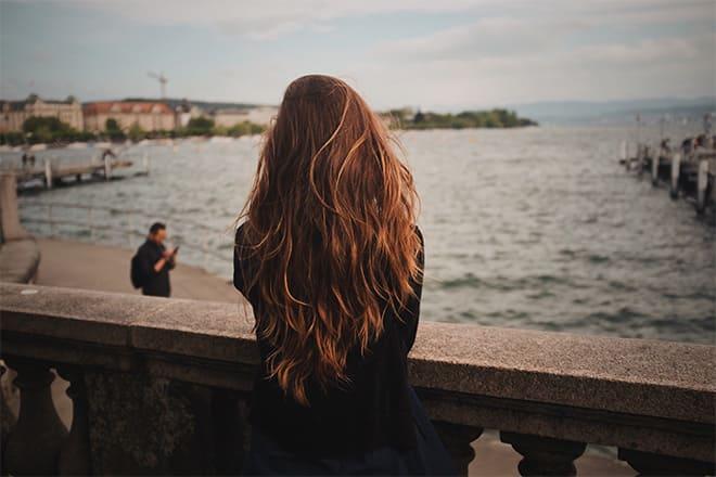 Mulher de costas, olhando para o mar, com cabelo de corte em camadas
