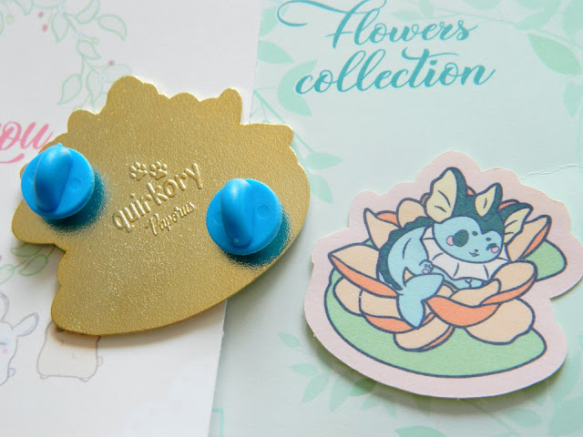 A photo of a pokemon enamel pin by Quirkory. Vaporeon is sitting on a lotus flower, a sticker of this design can be seen as well as the back of the pin with blue rubber backs