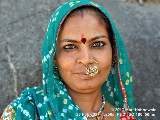 matt hahnewald photography; facing the world; face; forehead; bindi; eye makeup; tilaka; third eye; eyes; talkative eyes; nose; nose piercing; nose jewelry; nose ring; facial expression; eye contact; shawl; dupatta; headscarf; sindoor; consent; empathy; rapport; emotion; respect; ethnic; traveling; traditional; cultural; hinduism; folklore; pilgrim; temple; mount girnar; bhavnath; junagadh; gujarat; western india; indian; one person; female; adult; middle-aged; mature; woman; married; picture; photo; illustrative editorial; educational; nikon d3100; nikkor af-s 50mm f/1.8g; prime lens; 50mm lens; 4x3; horizontal; street; portrait; closeup; head shot; full-face view; green; outdoors; color; posing; authentic; smiling; charming; alamy
