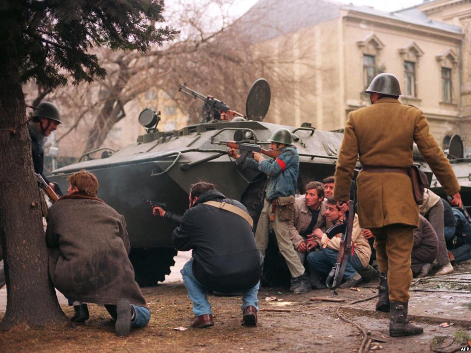 A group of anti-Communist civilian fighters along with a Romanian soldier supporting anti-Ceausescu's activists, protect themselves behind an armoured personnel carrier from snipers fire shot by the supposedly Securitate secret police agents loyal to the communist power .