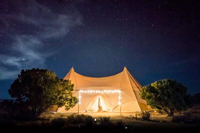 Carpa para boda instalada en espacio natural y con iluminación en el acceso