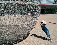 Little boy pushing up with his arms outstretched under the side of a large metal wire globe