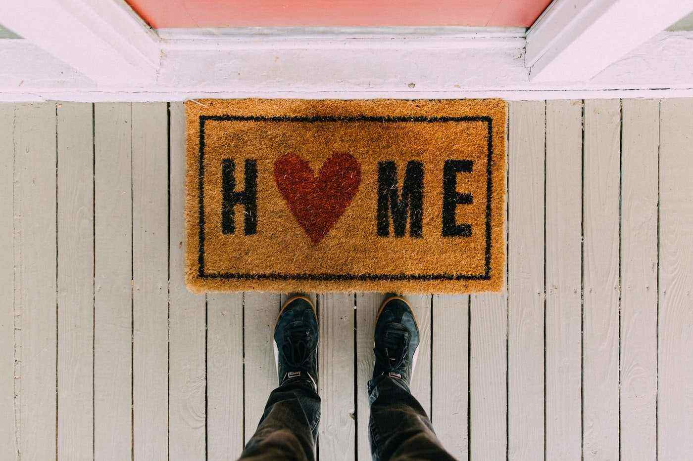 top view of feet and welcome mat on porch - how to travel the world without leaving your home