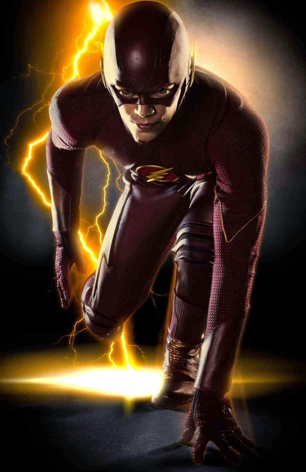 Grant Gustin in costume as The Flash, left arm and left leg lurched forward touching the ground with right side of his body moved back