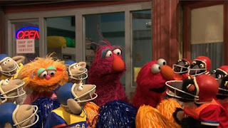 There are two football teams The Sheep and The Penguins. Elmo, Zoe and Telly cheer for them. Sesame Street Episode 4420, Three Cheers for Us, Season 44