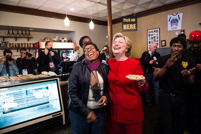 image of Hillary Clinton with a Black woman supporter, at a soul food joint on the campaign trail; the two women are laughing uproariously