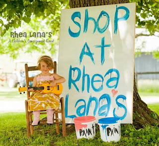 "a preschool girl in a colorful dress plays with a guitar next to a painted sign that says ""shop at Rhea Lana's"""