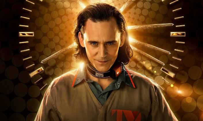 Imagem: fundo de padrão marrom com dourado e um relógio, e na frente, o personagem Loki, interpretado por Tom Hiddleston, um homem branco e magro, de olhos azuis e longos cabelos pretos, em um uniforme de prisioneiro bege com detalhes vermelhos e uma coleira eletrônica no pescoço.