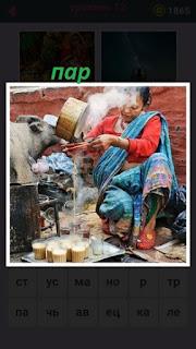 женщина готовит и выливает горячую воду с паром идущим из кастрюли