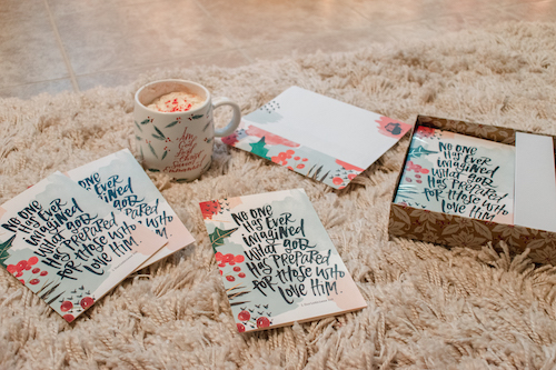 No One Has Ever Imagined Christmas cards scattered on floor with Names Of Jesus mug nearby.