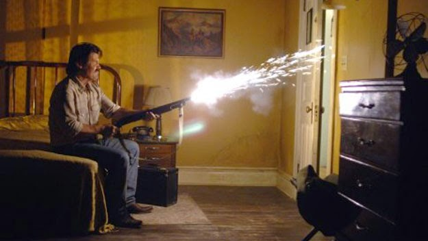 Josh Brolin as Llewelyn Moss opens fire in a motel room, in No Country for Old Men (2007), Directed by Joel and Ethan Coen