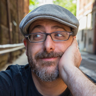 Author photo - He has a short beard and mustache. He has a slight smile and is looking to the side. He's wearing glasses and a pageboy hat.  He's wearing a