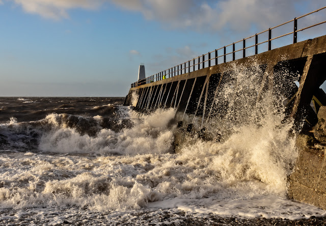 Photo of another view of the waves breaking against the pier
