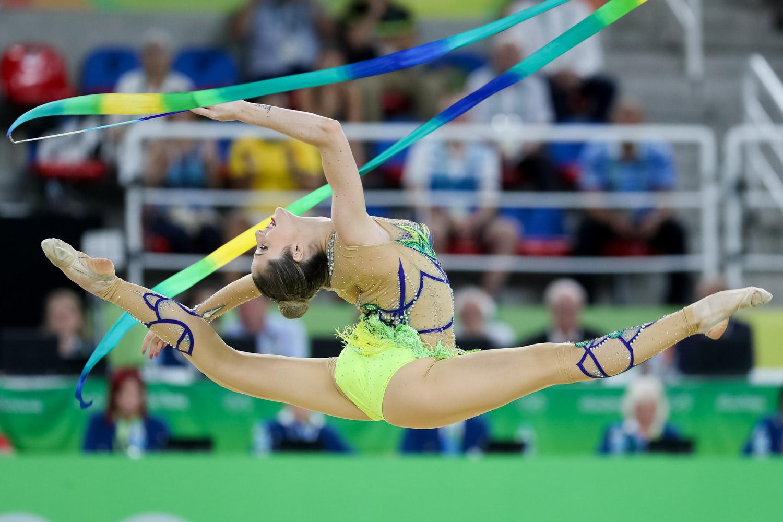 Natália Gaudio se apresenta com a fita na Rio 2016. Ela usa collant e fitas coloridos em tons de verde, azul e amarelo