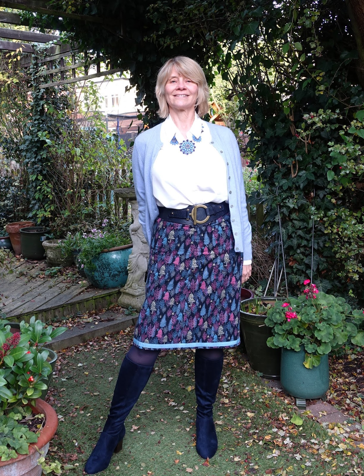 Over-50s fashion blogger Gail Hanlon from Is This Mutton shows how a formerly boring outfit of a print skirt and long cardigan is improved with a wide belt, necklace and long round toed boots