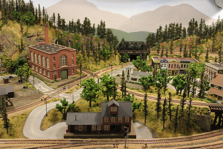 A completed 4 x 8 HO scale model railroad layout and scenery set in a mountain forest scene