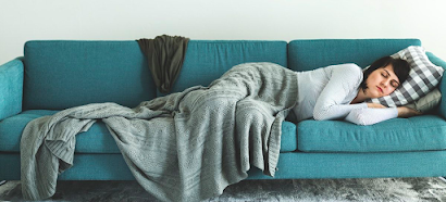 A teal sofa with a caucasian woman with short brown hair sleeping with a grey blanket over her