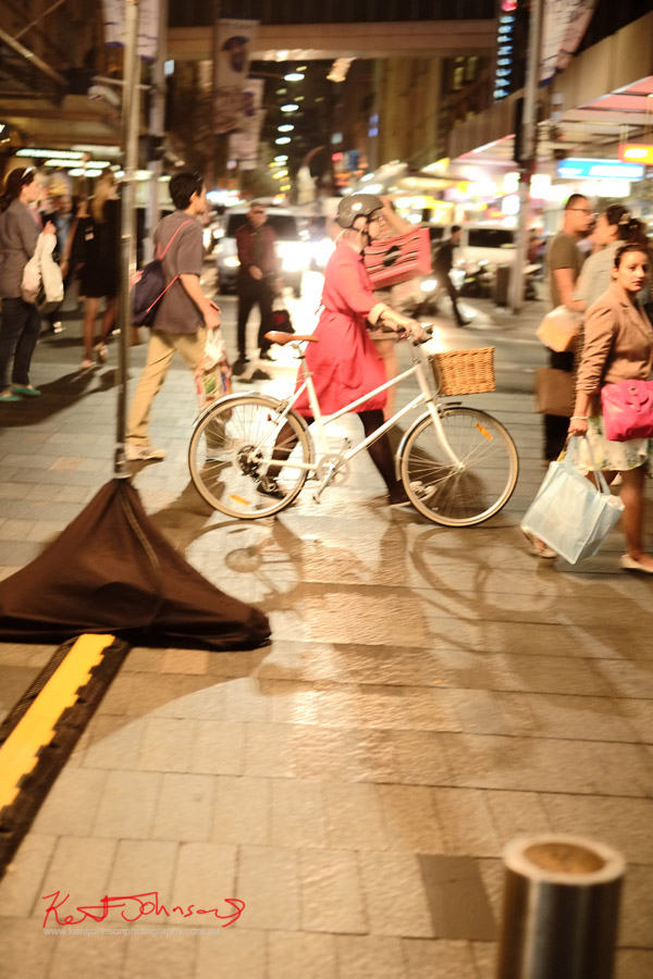 Lady bike commuter wearing a red trench coat, walking bike - VFNO 2013 Pitt Street Mall - VOGUE Fashion Night Out Sydney