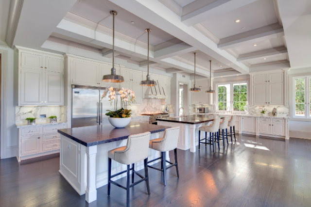 White gourmet kitchen coffered ceiling silver pendant lights stainless appliances white barstools with nail head trim marble counter tops