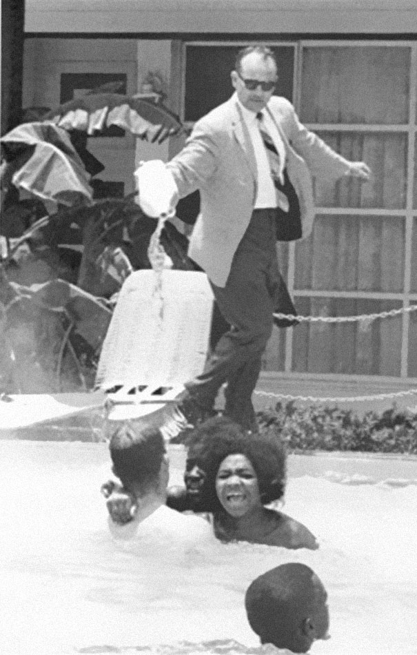 Hotel owner pouring acid in the pool while black people swim in it, ca. 1964