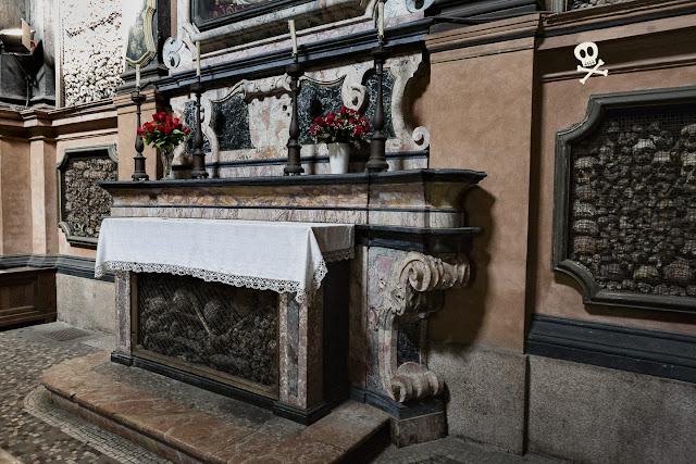 Altar de San Bernardino alle Ossa, lleno de huesos de diferentes partes del cuerpo, sin aparente orden de colocación.