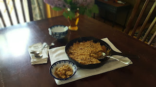 rhubarb crisp in cast iron pan with lilacs in the background